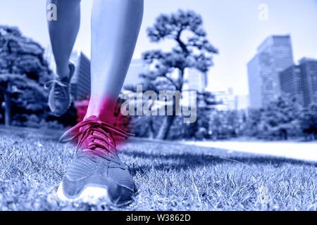 Lesioni sportive - runner piedi con dolore alla caviglia. Primo piano delle scarpe da corsa di atterraggio su dolce erba con il cerchio rosso mostra danneggiando le articolazioni e i legamenti causato da un trauma per il fitness. Foto Stock