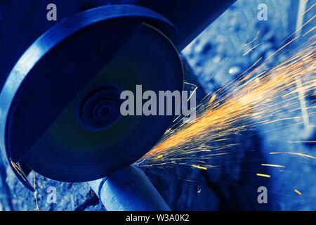 Segatura di tubo di metallo con una sega elettrica. La formazione di scintille volare. Tonificazione in blu