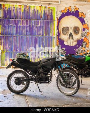 Garage con una moto su una parete multicolore e vernice di un cranio Foto Stock
