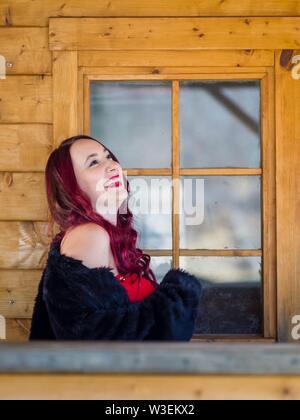 Attraente redhaired ritratto femminile gigling guardando verso l'alto lontano da parte Foto Stock