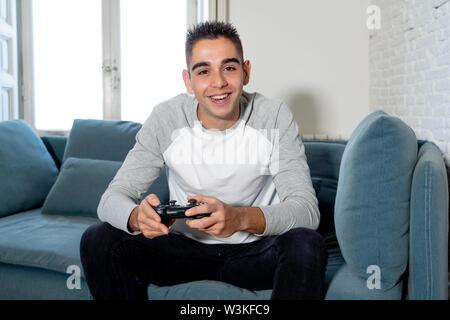 Ritratto di giovane studente uomo i video-giochi per divertirsi vincendo il gioco utilizzando il telecomando wireless joystick con freak intensa faccia felice nella gam maschio Foto Stock
