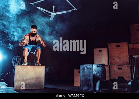 Montare tattoed uomo barbuto di saltare su una scatola come parte di esercizio di routine. Uomo casella facendo saltare in palestra. Atleta sta eseguendo la casella salta. Foto Stock