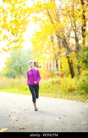 Lo stile di vita di autunno donna in esecuzione nella foresta di caduta con belle foglie gialle fogliame. A piena lunghezza Ritratto di runner jogging all'aperto sulla strada forestale. Razza mista asiatica ragazza caucasica nel suo 20s. Foto Stock