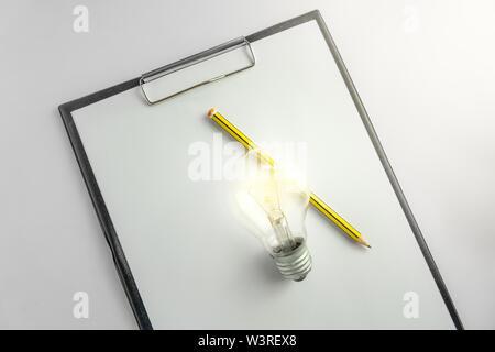 Carta bianca con un bulbo di luce e matita in attesa di idea concetto con luce Foto Stock