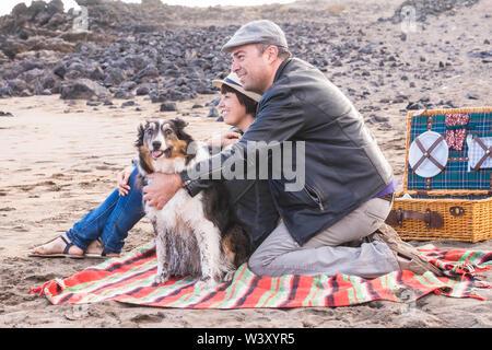 Adulto felice famiglia persone soggiorno insieme alla spiaggia con divertente adorabile cane sporca - la felicità all'aperto e attività per il tempo libero per uomo e donna in amore Foto Stock