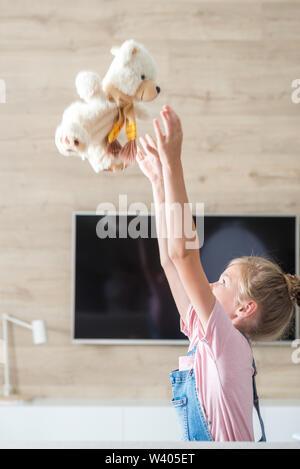 Bellissima bambina sul divano abbracciando Teddy bear. Il concetto di una infanzia felice, gioco in famiglia. Foto Stock