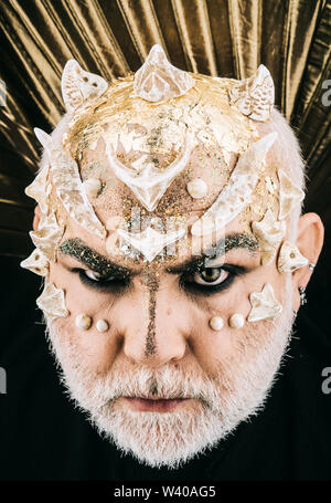 Closeup demon faccia con il male gli occhi su sfondo nero. Monster con spine e le verruche sulla testa. Una creatura mistica con pelle dorata oltre, magica bestia, Foto Stock