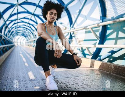 Giovane donna runner riposo dopo la esecuzione di allenamento. Femmina modello fitness accovacciato su un ponte. Foto Stock