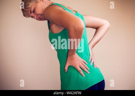 Donna con capelli corti si senta forte dolore nel retro isolato. La gente, la sanità e la medicina concept