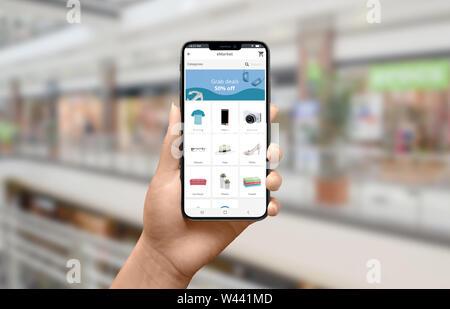 Shopping in linea con il concetto di smartphone. Moderno negozio online sito web app sul telefono. City Mall, Centro in background. Close-up. Foto Stock