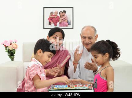 Ragazzo e ragazza che giocano a Ludo con i loro nonni