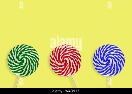 Dolce lecca lecca. Round grande caramella. Tre multi-caramelle colorate su sfondo giallo. Verde, Blu e Rosso Foto Stock