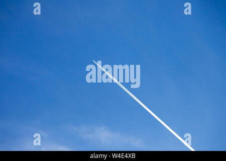 Guardando al di sopra nella bellissima luminoso cielo blu, con un aeroplano vola alto lasciando contrails dietro nel suo percorso Foto Stock