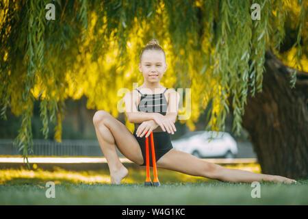 Ragazza ginnasta esegue un esercizio con bastoni di ginnastica sul prato nel parco. Foto Stock