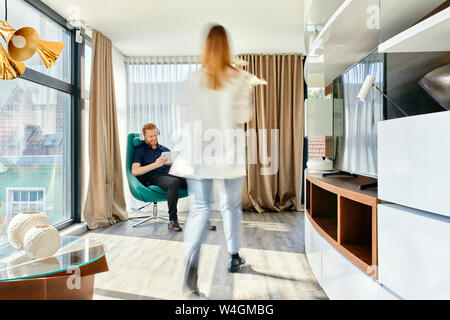 Giovane a casa, uomo che ascolta musica, donna che porta Vaso con fiori Foto Stock