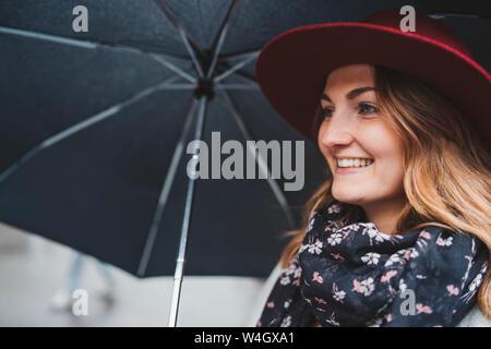 Ritratto di felice giovane donna sotto l ombrello