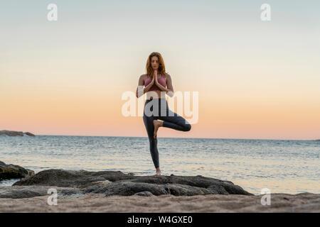 Giovane donna a praticare yoga sulla spiaggia, facendo la posizione dell'albero, durante il tramonto in spiaggia tranquilla, Costa Brava, Spagna Foto Stock