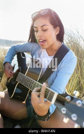 Giovane donna di cantare e suonare la chitarra sulla spiaggia