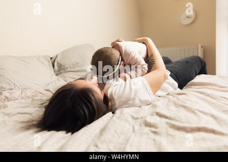 I giovani la madre e il bambino sono a letto. Mamma e Bambino giocano in casa. Stile di vita autentica foto. Foto Stock