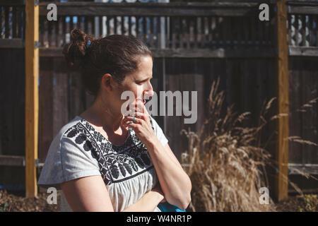 La donna sta di fronte al recinto in presenza di luce solare con espressione pensosa Foto Stock
