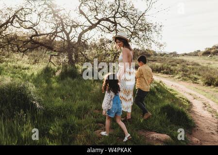 Vista laterale della madre e bambini a piedi in campo insieme Foto Stock