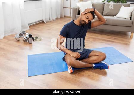 Uomo di formazione e corpo di stiro a casa