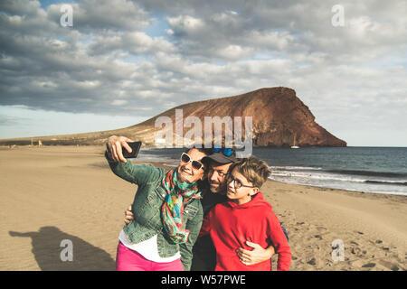 Papà mamma con figlio tenendo selfie sorridente e felice in spiaggia vicino all'oceano. I genitori con bambini in vacanza facendo fotografie per memorie di un esotico