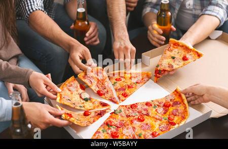 Gruppo di amici condividendo la pizza insieme al partito di casa