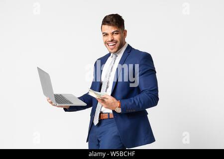 Uomo gioioso in tuta Holding portatile e denaro per celebrare il successo Foto Stock