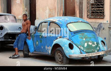 Giovane ragazzo cubano si appoggia contro una ben indossati degli anni cinquanta era Volkswagen maggiolino su un angolo di strada di Havana, Cuba Foto Stock