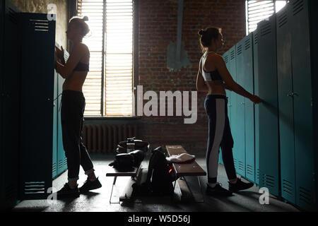 Vista laterale di due dure le donne in shabby cambiando stanza in sports club , spazio di copia Foto Stock