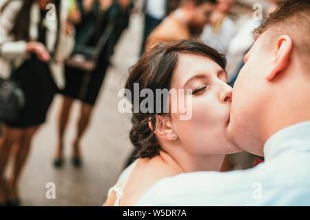 Bella Sposa e lo sposo abbracciando e baciando il giorno delle nozze all'esterno. Concetto di nozze, nuova famiglia.
