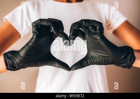 Le femmine le mani in nero Guanti in lattice mostra forma di cuore. Giovani slim tan donna tshirt bianco e nero guanti.