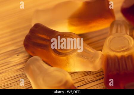 Una macro ritratto di alcuni dolci colorati conformato come bottiglie di cola. I dolci sono disposti su un asse di legno. Foto Stock