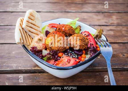 Israeliano di cibo di strada. Insalata di falafel con hummus, la barbabietola e la verdura in una ciotola in un ristorante. Foto Stock