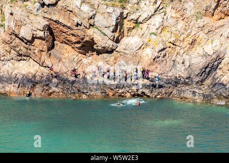Un gruppo di giovani coasteering sotto le scogliere a Pointe de la Moye, le Gouffre, Les Villets sulla bella, robusta costa sud dell'isola di Guernsey REGNO UNITO Foto Stock