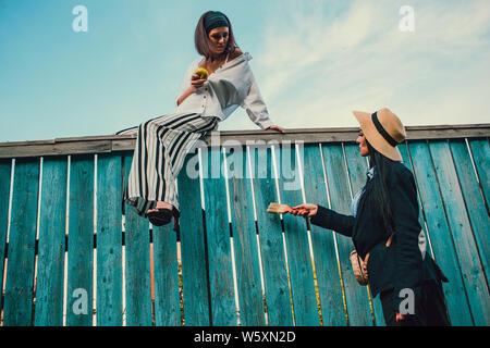 Tom Sawyer Pretty Woman nel cappello di paglia davanti al recinto. La donna dipinta una staccionata di legno. Foto Stock