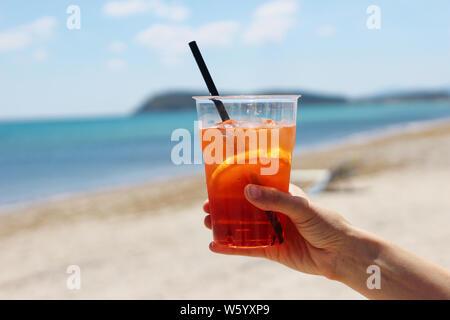 Primo piano della mano womans holding refrigerate aperol coctail con fetta di arancia, cannuccia e cubetti di ghiaccio, italiano la bevanda alcolica. Sfondo sfocato wit