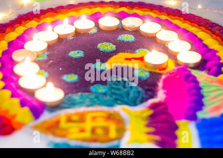 Bella rangoli realizzato da polveri colorate e decorate con candele di cera diyas il Diwali eve. Questi modelli sono realizzati a mano da indù e decorare