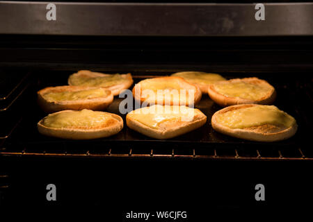 Fette di dolce formaggio cheddar sotto il grill fatta in casa di famiglia burger di notte. Il formaggio è giallo, panini sono il bianco e il forno è scuro Foto Stock