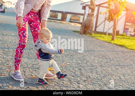 Carino poco adorabile bionda toddler boy facendo i primi passi con supporto madre presso il parco della città al tramonto di sera tempo. Happy funny bambino ad imparare a camminare