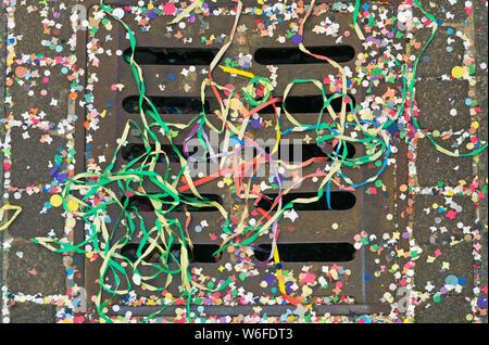 Carnevale coriandoli e peper streamers su un tombino Foto Stock