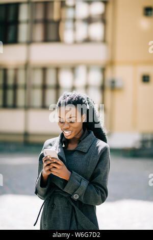 Giovane bella donna africana utilizzare il telefono in strada