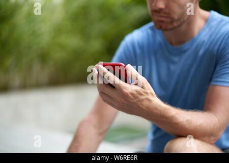 Candide lifestyle closeup colpo di bello con la barba uomo seduto tenendo cellulare la lettura dei messaggi di posta elettronica in blu athletic tshirt all'aperto Foto Stock