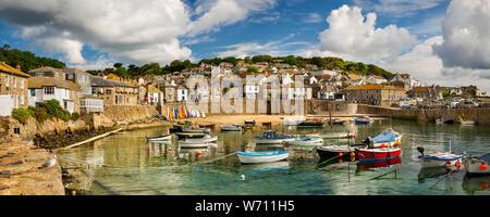 Regno Unito, Inghilterra, Cornwall, Mousehole, barche ormeggiate in porto a bassa marea sotto South Cliff, panoramica Foto Stock