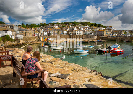 Regno Unito, Inghilterra, Cornwall, Mousehole, Il Wharf, giovane sul banco di banchina, ammirando le barche ormeggiate in porto Foto Stock