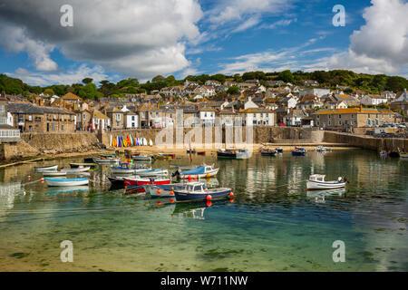Regno Unito, Inghilterra, Cornwall, Mousehole, barche ormeggiate in porto a bassa marea sotto South Cliff Foto Stock