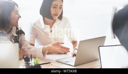 Due belle giovani asiatici imprenditrici scambiare le loro idee in una strategia di investimento con computer portatile Foto Stock