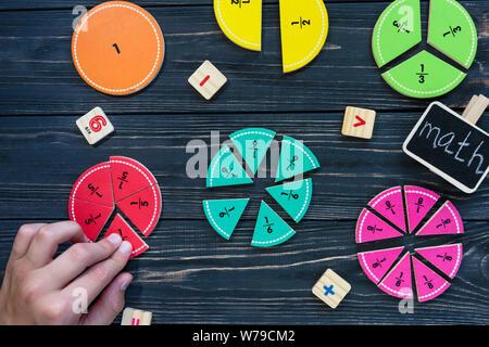 Bambini mano muove colorato frazioni matematica su legno scuro o di sfondo tabella. Interessante creative matematica divertente per i bambini. Istruzione, torna a scuola concep Foto Stock