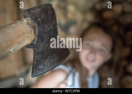 L'ascia sopra il bambino. Il bambino è al di fuori della messa a fuoco. Giovane ragazza guarda la ax con orrore. Il concetto di abuso domestico dei bambini. Foto Stock